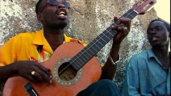 Jamaican Brushy One String Performs 'Chicken In The Corn' On One String Guitar